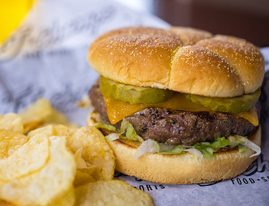hamburger with cheese, lettuce, pickles, and chips